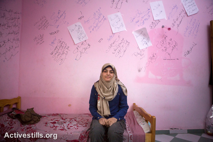 "Doa Naim, age 15, sits in front of her writings which cover the walls of her bedroom in her home which was damaged during the last Israel offensive, September 16, 2014. Doa says, ""By writing on the walls, I tried to say what I feel."" She started writing at onset of the war."