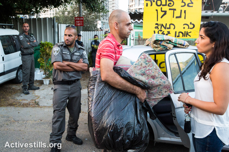 Members of the Halif family load their belongings into a car during the eviction of their family from its house in the Givat Amal neighborhood of Tel Aviv, September 17, 2014. Residents and community activists gathered in the neighborhood in an attempt to stop the eviction. The residents, who were placed there by the state in the 1950s, have been leading a struggle to recognize their rights to the property, which was sold to an Israeli businessman in the 1970s. More families in the neighborhood are also living under threat of eviction.