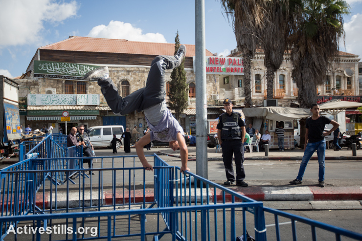 A parkour player preforms on a Israeli police fence, as Israeli policemen control access to the Al Aqsa Mosque in Jerusalem's Old City, preventing many Palestinian Muslim worshippers from attending Friday prayers, September 26, 2014. The Israeli police have restricted access to the Al-Aqsa Mosque compound, Islam's third-holiest shrine, to  men under 50 in an attempt to control clashes after Friday prayers.