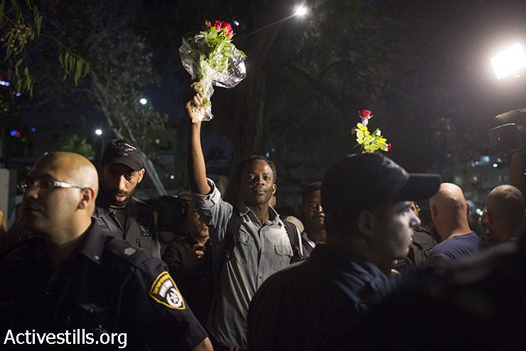 "African asylum seekers hold flowers as residents of south Tel Aviv and right-wing activists protest against the Israeli High Court decision to cancel the ""infiltrator law"" and close the Holot detention center, South Tel Aviv, October 5, 2014. (Activestills)"