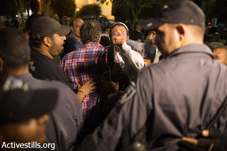 "Israeli right-wing activist Itamar Ben Gvir shouts at asylum seekers as residents of south Tel Aviv protest the Israeli High Court decision to cancel the ""infiltrator law"" and close the Holot detention center, in South Tel Aviv, October 5, 2014.(Activestills)"