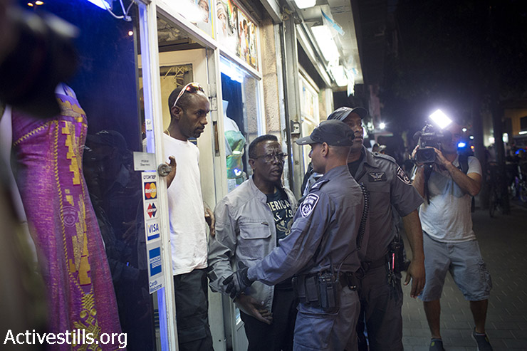 "An Ethiopian Jew is held back by policemen after protests tried to attack him as residents of south Tel Aviv and right-wing activists protest against the Israeli High Court decision to cancel the ""infiltrator law"" and close the Holot detention center, in South Tel Aviv, October 5, 2014. (Activestills)"
