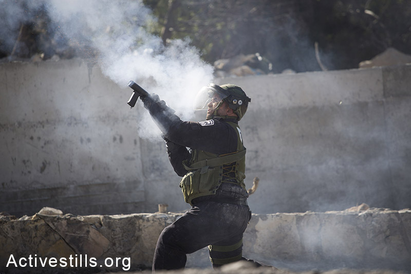An Israeli policeman shots tear gas as Palestinian youth throw stones during clashes in the neighbourhood of Issawia, East Jerusalem, October 24, 2014. Clashes have continued two days after a Palestinian man drove a car in to a crowd, killing a baby and injuring seven people in Jerusalem. (Activestills.org)