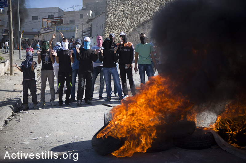 Palestinian youth burn tires during clashes in the neighbourhood of Issawia, East Jerusalem, October 24, 2014. Clashes have continued two days after a Palestinian man drove a car in to a crowd, killing a baby and injuring seven people in Jerusalem. (Activestills.org)