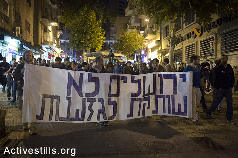 """A sign reading; """"Jerusalem is not silent towards racism"""", seen left wing activists during a protest in the city centre of West Jerusalem against racism, October 18, 2014. The action was organised following violent attacks of right wing activists on Palestinians in Jerusalem's city centre. (Activestills.org)"""