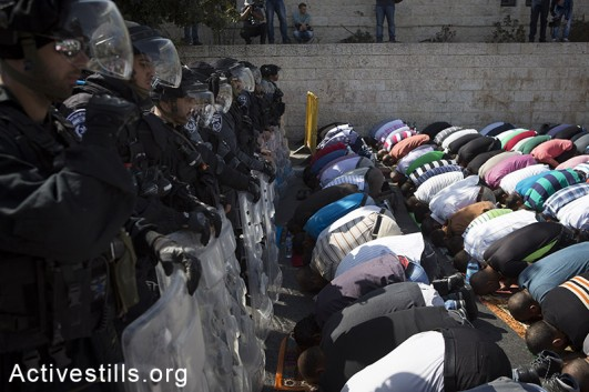 Palestinian Muslim worshipers perform traditional Friday prayers in a street in Wadi Joz neighborhood outside Jerusalem's Old City, as policemen block their way to Al Aqsa mosque, October 17, 2014. The Israeli government has restricted access to the Aqsa mosque compound, Islam's third holiest shrine to men under 50. (Activestills.org)