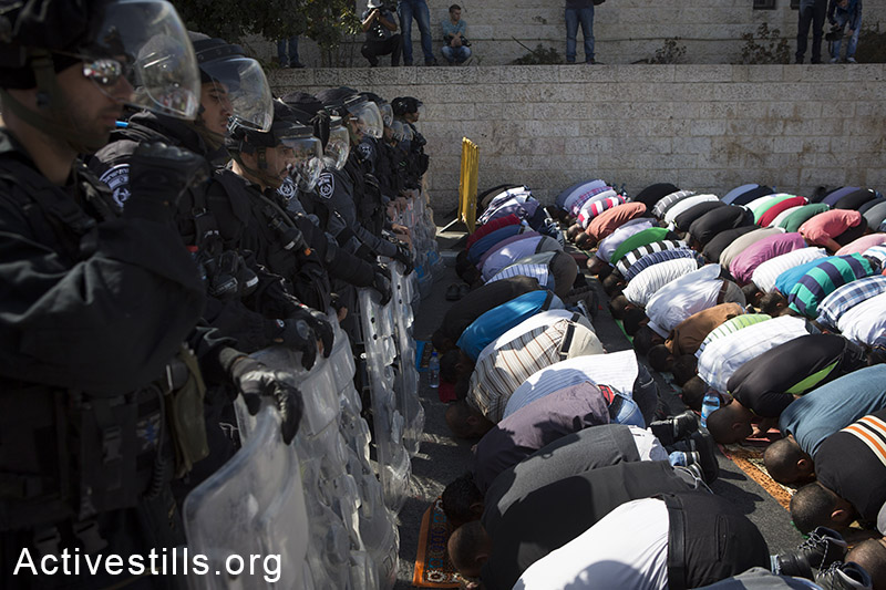 Palestinian Muslim worshipers perform traditional Friday prayers in a street in Wadi Joz neighbourhood outside Jerusalem's Old City, as policemen block their way to Al Aqsa mosque, October 17, 2014. The Israeli government has restricted access to the al-Aqsa mosque compound, Islam's third holiest shrine to men under 50. (Activestills.org)