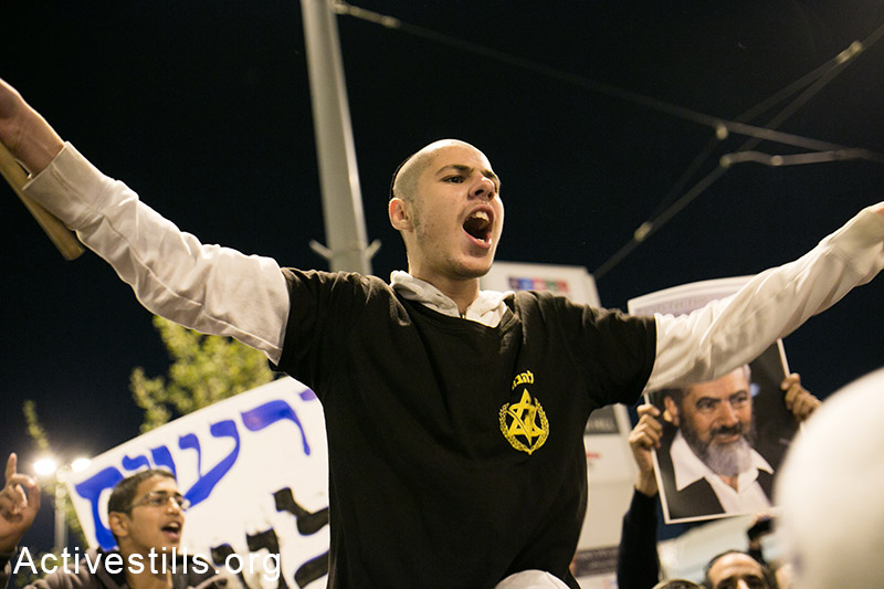 Right-wing Israeli activists, many of whom wore t-shirts identifying them with the far-right anti-miscegenation group Lehava, call for revenge at the scene of a deadly car attack in which a Palestinian man killed a baby and injured seven Israelis a day before, October 23, 2014. (Activestills.org)