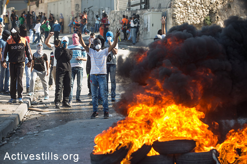 Palestinian youth seen burning tires during clashes with Israeli police in the neighbourhood of Issawia on October 24, 2014 in Jerusalem.