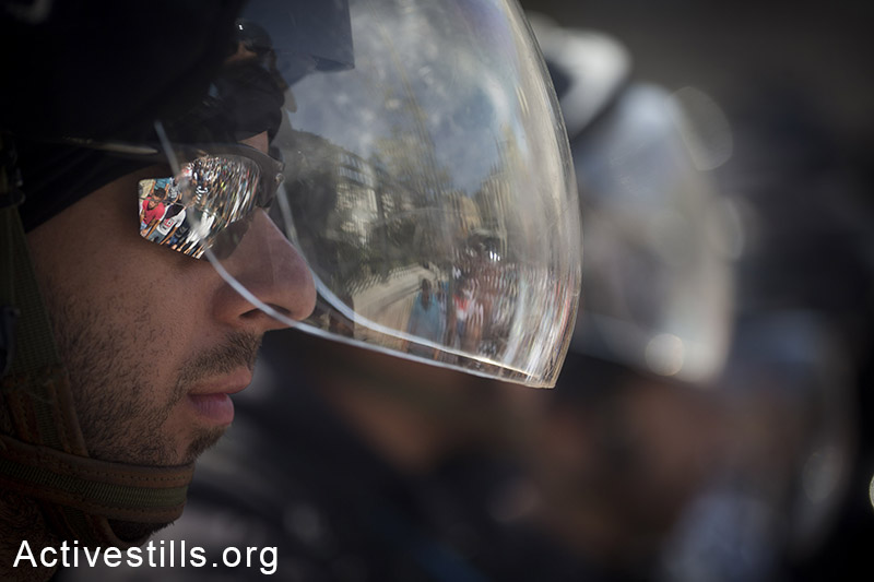 Palestinian Muslim worshipers are reflected on an Israeli policemen sunglasses, as they perform traditional Friday prayers in a street in Wadi Joz neighbourhood outside Jerusalem's Old City, as policemen block their way to Al Aqsa mosque, October 17, 2014. The Israeli government has restricted access to the al-Aqsa mosque compound, Islam's third holiest shrine to men under 50. (Activestills.org)