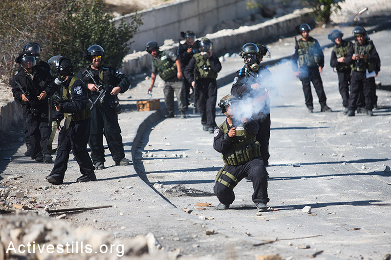 Israeli police shoot tear gas during clashes with Israeli police in the neighbourhood of Issawia on October 24, 2014 in Jerusalem. Clashes have continued two days after a Palestinian man drove a car in to a crowd, killing a baby and injuring seven people in Jerusalem. (Activestills.org)