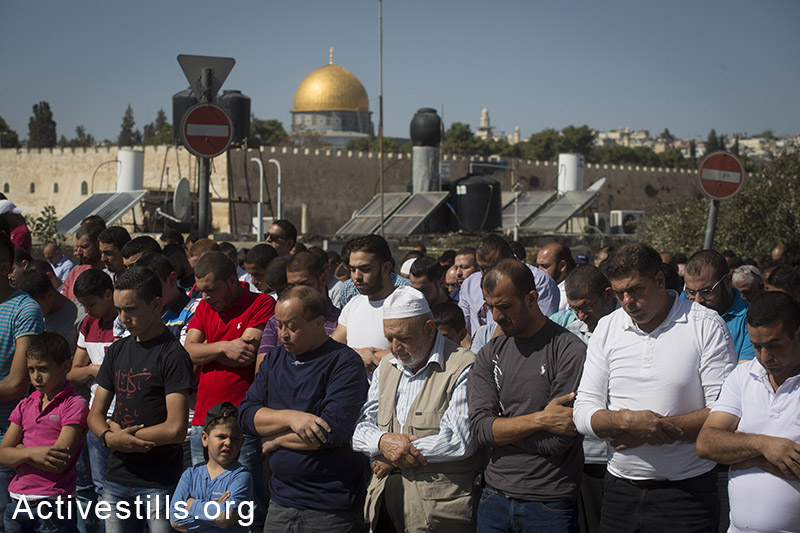 Palestinians perform Friday prayers in the Ras al-Amud neighborhood of East Jerusalem due to Israeli restrictions on access to the Aqsa Mosque for Palestinians under the age of 40, October 24, 2014. (Activestills.org)