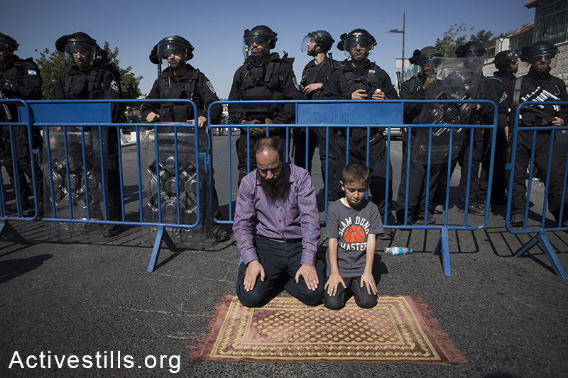 Palestinians perform Friday Prayer at the neighbourhood of Ras Al-Amud in East Jerusalem due to Israeli Government's entrance restriction to the al-Aqsa Mosque for the Palestinians under the age of 40, October 24, 2014. (Activestills.org)