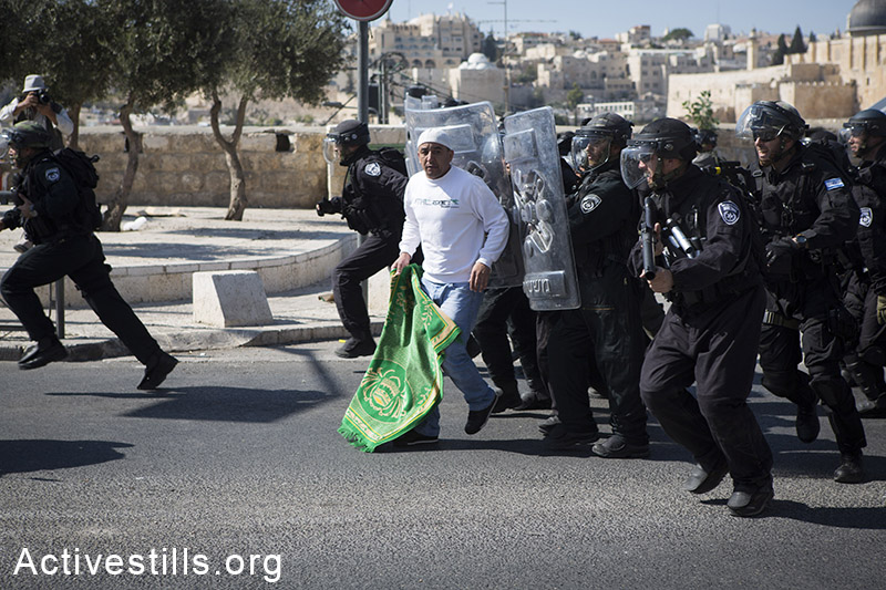 Israeli policemen push a Palestinian man at the end of the Friday prayers in the East Jerusalem neighborhood of Ras al-Amud, October 24, 2014.Israeli police barred the entrance to the Aqsa Mosque for Palestinians under the age of 40. (Activestills.org)