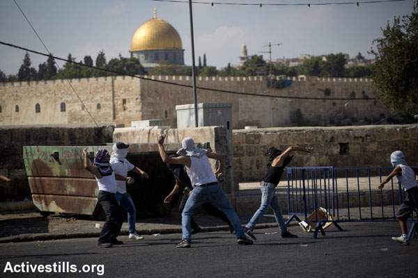 Palestinian youth throw stones during clashes in the East Jerusalem neighborhood of Ras al Amud, with the Aqsa Mosque seen in the background. (Photo by Oren Ziv/Activestills.org)