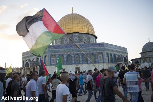 Palestinian youth hold a Palestinian flag outside the Aqsa Mosque in the Haram al-Sharif/Temple Mount compound, East Jerusalem. (Photo: Oren Ziv/Activestills.org)