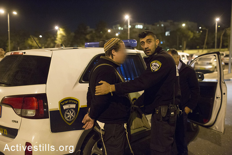 Israeli policemen arrest a right-wing activist during a protest calling for revenge at the East Jerusalem scene of a deadly car attack in which a Palestinian man killed a baby and injured seven Israelis a day before, October 23, 2014. (Activestills.org)