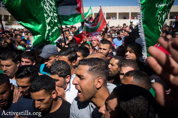 Palestinians shout slogans as they carry the body of 14-year-old Palestinian-American Orwah Hammad at his funeral in the West Bank village of Silwad, October 26, 2014. (Photo by Oren Ziv/Activestills.org)