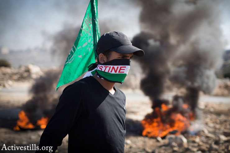 A Palestinian youth is seen during clashes with the Israeli army following the funeral of 14-year-old Palestinian-American Orwah Hammad in the West Bank village of Silwad, October 26, 2014. (Photo by Oren Ziv/Activestills.org)