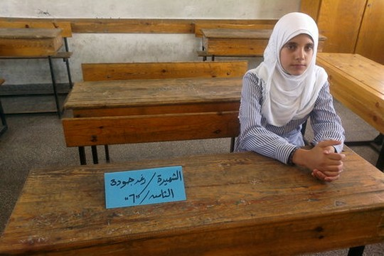 Rawan Sabah sits next to where her friend, Raghed Joudah, used to sit in class. Joudah was killed by an Israeli airstrike along with five of her family members. (photo: Awni Farhat)