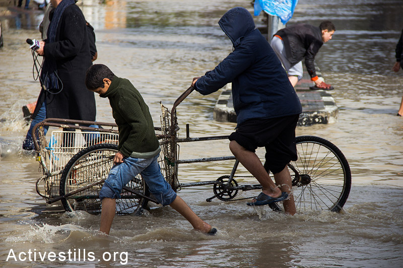 Residents of Al-Nafaq in high waters flooding the neighborhood, Gaza City, November 27, 2014. Basel Yazouri/Activestills.org