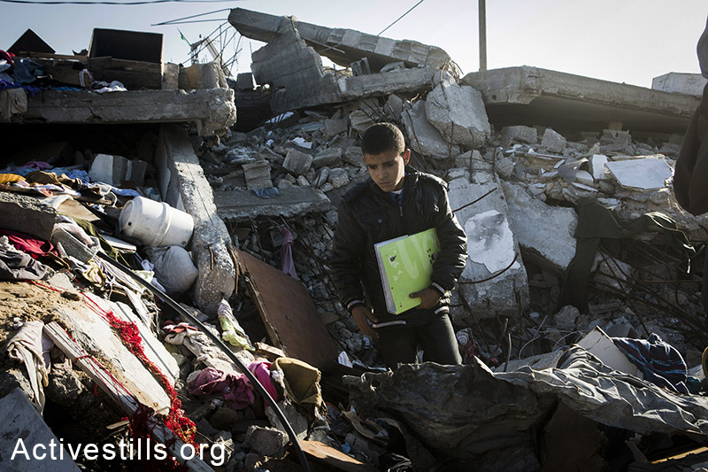 A Palestinian child from Wadhan family picks up a book in the rubble of the destroyed home of his relatives, in the city of Beit Hanoun, Northern Gaza city, November 10, 2014. Eight members of the Wadhan family, mostly women and children were killed. Israeli forces attacked after family members were told to stay inside the house. Many Palestinians in the Gaza Strip face hard living conditions following the seven-week Israeli offensive during which 2,131 Palestinians were killed, and an estimate of 18,000 housing units have been either destroyed or severely damaged, leaving more than 108,000 people homeless. Palestinians in one of the new established camp with metal caravan shelters for displaced people in the village of Khuza'a, eastern Gaza Strip, November 9, 2014. Many Palestinians in the Gaza Strip face hard living conditions following the seven-week Israeli offensive during which 2,131 Palestinians were killed, and an estimate of 18,000 housing units have been either destroyed or severely damaged, leaving more than 108,000 people homeless. Metal caravan shelters are seen on top of a destroyed home in the city of Beit Hanoun, Northern Gaza city, November 10, 2014. Many Palestinians in the Gaza Strip face hard living conditions following the seven-week Israeli offensive during which 2,131 Palestinians were killed, and an estimate of 18,000 housing units have been either destroyed or severely damaged, leaving more than 108,000 people homeless. Majda Bashir with three of her children, stand in the classroom where she stays with her family in the UNRWA al Mazra'a preparatory girls school, in the city of Deir al-Balah, eastern Gaza Strip, November 7, 2014. According to Majda, her family does not receive any food aid because the government was late to register the destruction of their home, preventing them to get on the list of beneficiaries. Several of her children suffer from malnutrition. Around 1,400 displaced Palestinians live in the school in very precarious conditions. Many Palestinians in the Gaza Strip face hard living conditions following the seven-week Israeli offensive during which 2,131 Palestinians were killed, and an estimate of 18,000 housing units have been either destroyed or severely damaged, leaving more than 108,000 people homeless. A destroyed living home in the home of al Talal Al Helu in Shujayea neighborood, eastern Gaza city, November 10, 2014. Talal Al Helu lost 11 members of his family, in an attack on his brothers' home. Many Palestinians in the Gaza Strip face hard living conditions following the seven-week Israeli offensive during which 2,131 Palestinians were killed, and an estimate of 18,000 housing units have been either destroyed or severely damaged, leaving more than 108,000 people homeless. Palestinians salvage materials at night from destroyed homes in the village of Khuza'a, eastern Gaza Strip, November 6, 2014. Many Palestinians in the Gaza Strip face hard living conditions following the seven-week Israeli offensive during which 2,131 Palestinians were killed, and an estimate of 18,000 housing units have been either destroyed or severely damaged, leaving more than 108,000 people homeless. Clothes hanged out in the village of Khuza'a, eastern Gaza Strip, November 6, 2014. Many Palestinians in the Gaza Strip face hard living conditions following the seven-week Israeli offensive during which 2,131 Palestinians were killed, and an estimate of 18,000 housing units have been either destroyed or severely damaged, leaving more than 108,000 people homeless. Ibtisam Al Najjar seen at the entrance to the basement where she and her family sleep in the village of Khuza'a, eastern Gaza Strip, November 6, 2014. Their home is half destroyed with the first floor having totally collapsed on the ground floor, forcing the 7 members of the family to sleep in the basement in very unsafe conditions. Many Palestinians in the Gaza Strip face hard living conditions following the seven-week Israeli offensive during which 2,131 Palestinians were killed, and an estimate of 18,000 housing units have been either destroyed or severely damaged, leaving more than 108,000 people homeless. A Palestinian woman sits near a fire in the new established camp with caravans for displaced people in the village of Khuza'a, eastern Gaza Strip, November 6, 2014. More than 200 Palestinians live in precarious conditions in the 26 caravans. Many Palestinians in the Gaza Strip face hard living conditions following the seven-week Israeli offensive during which 2,131 Palestinians were killed, and an estimate of 18,000 housing units have been either destroyed or severely damaged, leaving more than 108,000 people homeless. Jaber Abu Sa'eed, a 70-years old Nakba survivor, sits on his land, in the village of Juhor ad-Dik, eastern Gaza Strip, November 6, 2014. His home, located just 300 meters from the border, was demolished by the Israeli army during this summer. Many Palestinians in the Gaza Strip face hard living conditions following the seven-week Israeli offensive during which 2,131 Palestinians were killed, and an estimate of 18,000 housing units have been either destroyed or severely damaged, leaving more than 108,000 people homeless. A woman from Abu Sa'eed family stands in the kitchen of her new tin home, in the village of Juhor ad-Dik, eastern Gaza Strip, November 6, 2014. Their home, located just 300 meters from the border, was demolished by the Israeli army during Operation Protective Edges military offensive on Gaza. Many Palestinians in the Gaza Strip face hard living conditions following the seven-week Israeli offensive during which 2,131 Palestinians were killed, and an estimate of 18,000 housing units have been either destroyed or severely damaged, leaving more than 108,000 people homeless. A child coming out of his destroyed home in the village of Khuza'a, eastern Gaza Strip, November 7, 2014. Six family members stay in the living room, which is the only room which was not destroyed. Big holes in the walls have been barely covered by pieces of wood and plastic sheet. Many Palestinians in the Gaza Strip face hard living conditions following the seven-week Israeli offensive during which 2,131 Palestinians were killed, and an estimate of 18,000 housing units have been either destroyed or severely damaged, leaving more than 108,000 people homeless.  Anne Paq/Activestills.org