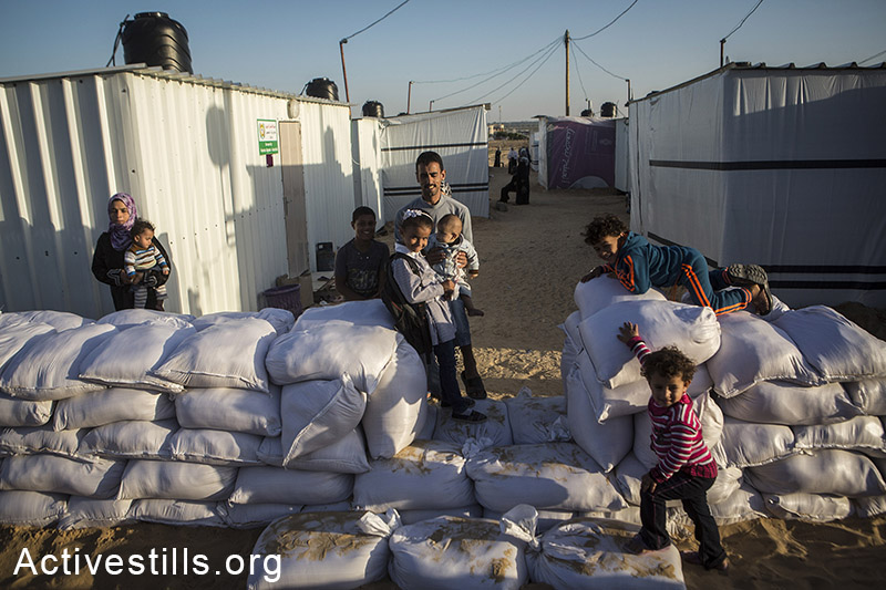 Palestinians in one of the new established camp with metal caravan shelters for displaced people in the village of Khuza'a, eastern Gaza Strip, November 9, 2014. Anne Paq/Activestills.org