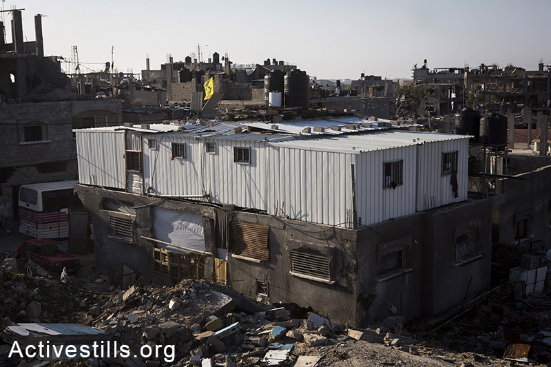 Metal caravan shelters are seen on top of a destroyed home in the city of Beit Hanoun, Northern Gaza city, November 10, 2014.  Anne Paq/Activestills.org