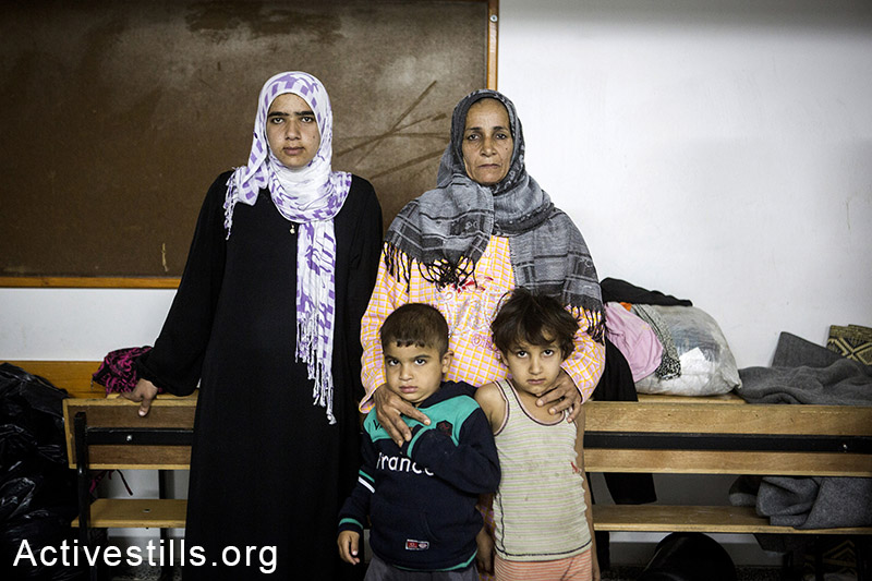 Majda Bashir with three of her children, stand in the classroom where she stays with her family in the UNRWA al Mazra'a preparatory girls school, in the city of Deir al-Balah, eastern Gaza Strip, November 7, 2014. According to Majda, her family does not receive any food aid because the government was late to register the destruction of their home, preventing them to get on the list of beneficiaries. Several of her children suffer from malnutrition. Around 1,400 displaced Palestinians live in the school in very precarious conditions. Anne Paq/Activestills.org