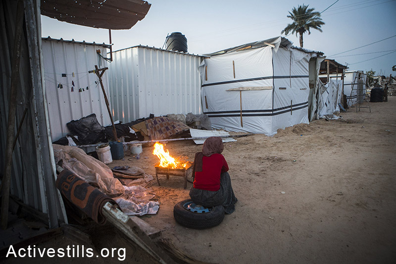 A Palestinian woman sits near a fire in the new established camp with caravans for displaced people in the village of Khuza'a, eastern Gaza Strip, November 6, 2014. More than 200 Palestinians live in precarious conditions in the 26 caravans. Many Palestinians in the Gaza Strip face hard living conditions following the seven-week Israeli offensive during which 2,131 Palestinians were killed, and an estimate of 18,000 housing units have been either destroyed or severely damaged, leaving more than 108,000 people homeless. Jaber Abu Sa'eed, a 70-years old Nakba survivor, sits on his land, in the village of Juhor ad-Dik, eastern Gaza Strip, November 6, 2014. His home, located just 300 meters from the border, was demolished by the Israeli army during this summer. Many Palestinians in the Gaza Strip face hard living conditions following the seven-week Israeli offensive during which 2,131 Palestinians were killed, and an estimate of 18,000 housing units have been either destroyed or severely damaged, leaving more than 108,000 people homeless. A woman from Abu Sa'eed family stands in the kitchen of her new tin home, in the village of Juhor ad-Dik, eastern Gaza Strip, November 6, 2014. Their home, located just 300 meters from the border, was demolished by the Israeli army during Operation Protective Edges military offensive on Gaza. Many Palestinians in the Gaza Strip face hard living conditions following the seven-week Israeli offensive during which 2,131 Palestinians were killed, and an estimate of 18,000 housing units have been either destroyed or severely damaged, leaving more than 108,000 people homeless. A child coming out of his destroyed home in the village of Khuza'a, eastern Gaza Strip, November 7, 2014. Six family members stay in the living room, which is the only room which was not destroyed. Big holes in the walls have been barely covered by pieces of wood and plastic sheet. Many Palestinians in the Gaza Strip face hard living conditions following the seven-week Israeli offensive during which 2,131 Palestinians were killed, and an estimate of 18,000 housing units have been either destroyed or severely damaged, leaving more than 108,000 people homeless.  Anne Paq/Activestills.org