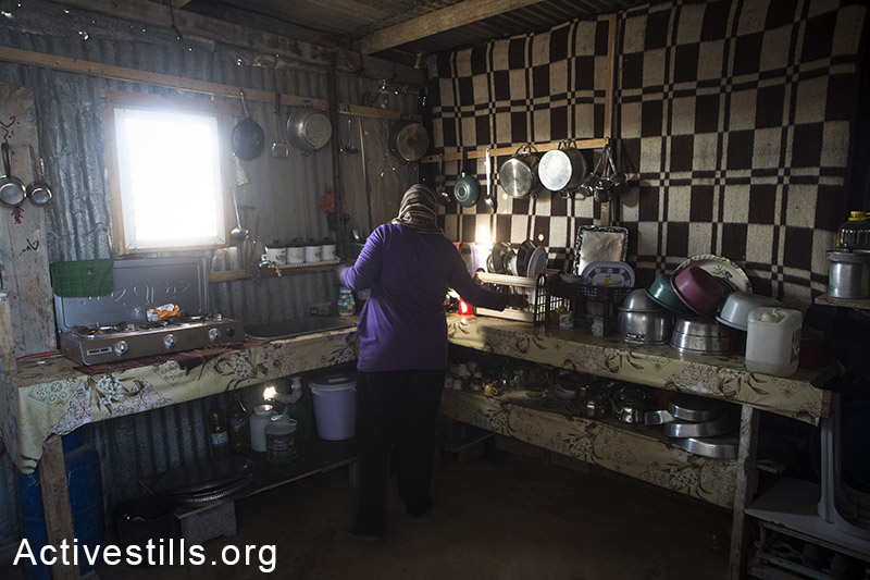 A woman from Abu Sa'eed family stands in the kitchen of her new tin home, in the village of Juhor ad-Dik, eastern Gaza Strip, November 6, 2014. Their home, located just 300 meters from the border, was demolished by the Israeli army during Operation Protective Edges military offensive on Gaza. Many Palestinians in the Gaza Strip face hard living conditions following the seven-week Israeli offensive during which 2,131 Palestinians were killed, and an estimate of 18,000 housing units have been either destroyed or severely damaged, leaving more than 108,000 people homeless. A child coming out of his destroyed home in the village of Khuza'a, eastern Gaza Strip, November 7, 2014. Six family members stay in the living room, which is the only room which was not destroyed. Big holes in the walls have been barely covered by pieces of wood and plastic sheet. Many Palestinians in the Gaza Strip face hard living conditions following the seven-week Israeli offensive during which 2,131 Palestinians were killed, and an estimate of 18,000 housing units have been either destroyed or severely damaged, leaving more than 108,000 people homeless. Anne Paq/Activestills.org
