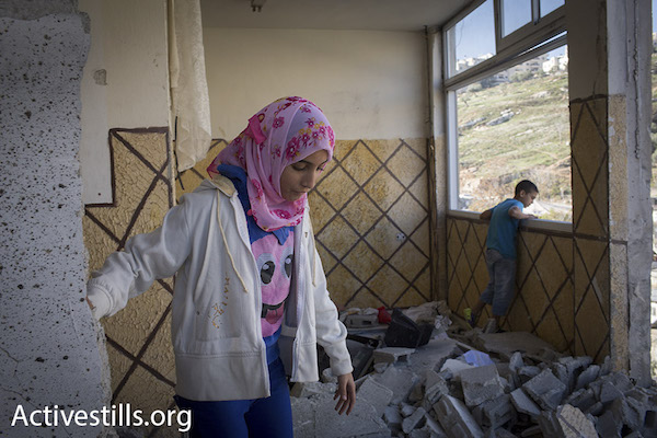 Family members of Abed al-Rahman Shaloudi, who murdered two people including a small baby, stand in their apartment that Israeli authorities demolished as part of a return to punitive home demolitions, Silwan, East Jerusalem, November 19, 2014. (Photo by Oren Ziv/Activestills.org)
