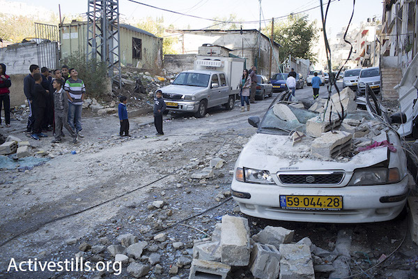 Local residents look at the rubble and damage after Israeli authorities demolished the home of Abed al-Rahman Shaloudi, who murdered two people including a small baby, Silwan, East Jerusalem, November 19, 2014. (Photo by Oren Ziv/Activestills.org)