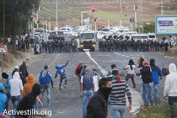 Arab youth clash with Israeli riot police in Kafr Kanna, Israel, November 8, 2014. The protests took place after an Arab man from the village was shot and killed by Israeli policemen. (Photo: Oren Ziv/Activestills.org)