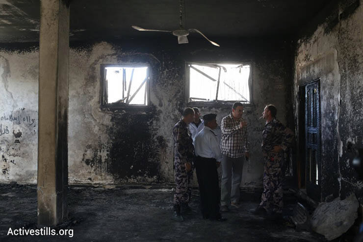 Local officials and Palestinian police stand in a mosque damaged in a suspected arson hate crime in the West Bank village of Al Mughayir, November 12, 2014. (Photo by Oren Ziv/Activestills.org)