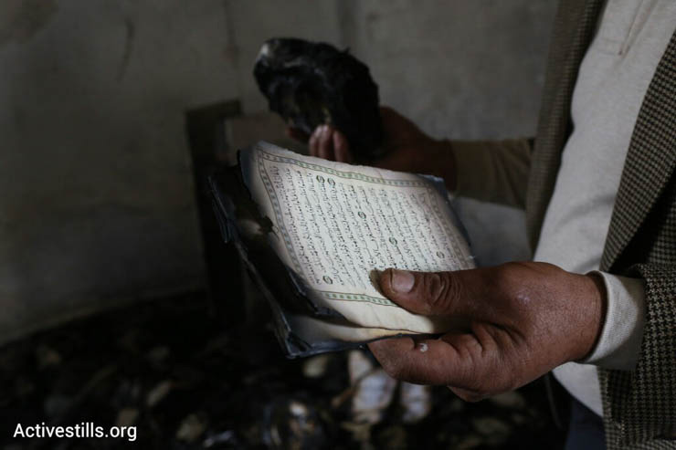 A man inspects a Quran damaged in a suspected arson hate crime against a mosque in the West Bank village of Al Mughayir, November 12, 2014. (Photo by Oren Ziv/Activestills.org)