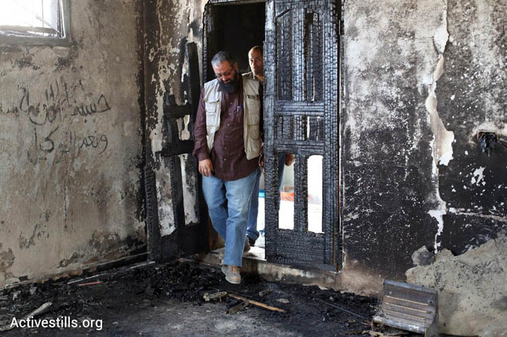 Palestinians enter a mosque damaged in a suspected arson hate crime in the West Bank village of Al Mughayir, November 12, 2014. (Photo by Oren Ziv/Activestills.org)