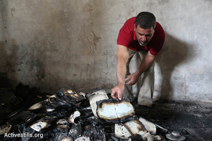 A man inspects Qurans damaged in a suspected arson hate crime against a mosque in the West Bank village of Al Mughayir, November 12, 2014. (Photo by Oren Ziv/Activestills.org)
