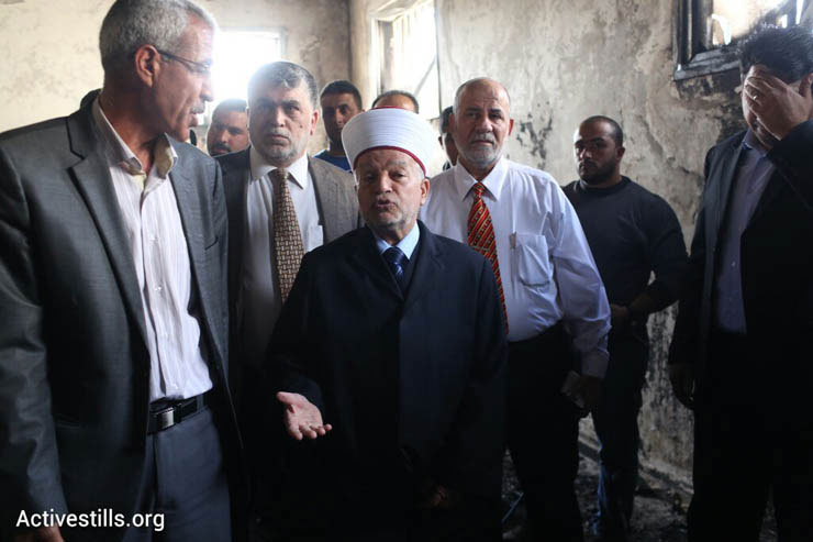 Local officials inspect the damage at a mosque hit in a suspected arson hate crime in the West Bank village of Al Mughayir, November 12, 2014. (Photo by Oren Ziv/Activestills.org)