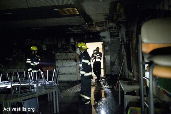 Firefighters in a classroom that was set on fire in the bilingual Hand In Hand school in Jerusalem, November 29, 2014. (Photo by Tali Mayer/Activestills.org)