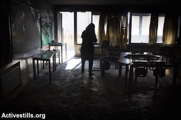 "A teacher inspects the damage from an arson attack that targeted first-grade classrooms at a Jewish-Arab school near the Palestinian neighborhood of Beit Safafa in southern Jerusalem, November 30, 2014. Spray painted on the walls were racist slogans in Hebrew reading: ""Death to Arabs"" and ""There's no coexistence with cancer"". (Photo by Oren Ziv/Activestills.org)"