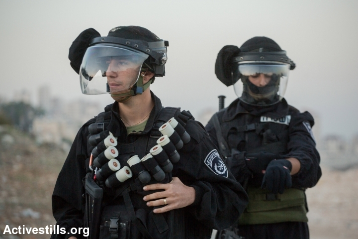 Israeli policemen are seen as Palestinian protestors and Israeli activists demonstrate against new concrete blockades put in place by Israeli police restricting access to the East Jerusalem neighbourhood of Issawiya, November 12, 2014. (Faiz Abu Rmeleh/Activestills.org)