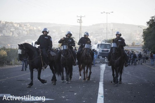 Police on horseback seen during clashes in the village of Kafr Kanna, in northern Israel. (Oren Ziv/Activestills.org)