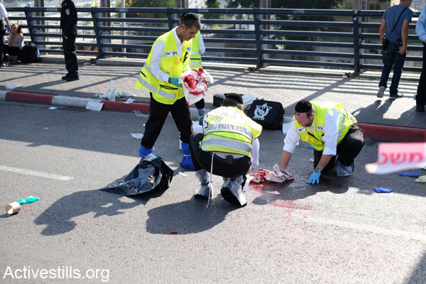 ZAKA volunteers collect blood from the spot where an Israeli soldier was stabbed Monday outside a Tel Aviv train station. (Photo by Yotam Ronen/Activestills.org)