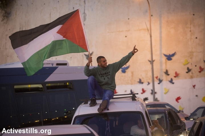 A Palestinian citizen of Israel waves a Palestinian flag during a protest against the police killing of Khir Hamdan in Umm al-Fahm. (photo: Oren Ziv/Activestills.org)