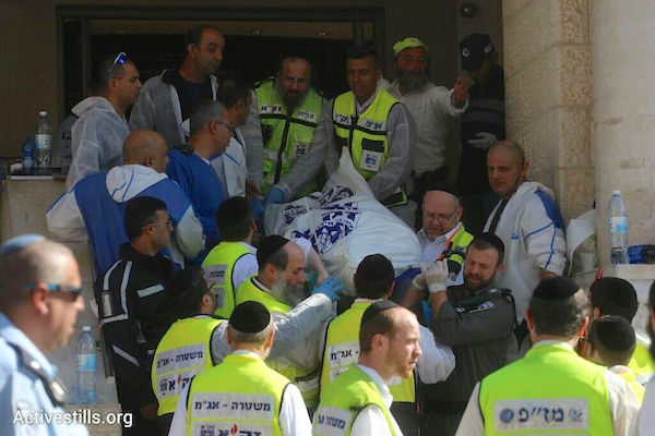 Israeli emergency personnel remove victims' bodies from the Jerusalem synagogue where two Palestinians killed four worshippers and seriously wounded seven others. (Photo by Oren Ziv/Activestills.org)