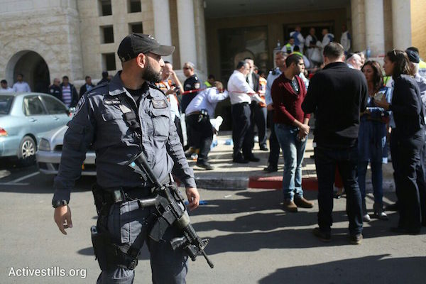 An Israeli police officer stands outside the Jerusalem synagogue where two Palestinians killed four worshippers and seriously wounded seven others, November 18, 2014. (Photo by Oren Ziv/Activestills.org)