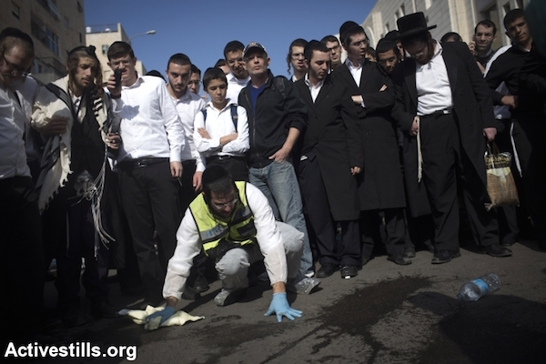 Israeli emergency services volunteers remove blood, according to Jewish tradition, from the scene of an attack by two Palestinians against Jewish worshippers at a synagogue in the ultra-Orthodox neighborhood of Har Nof in West Jerusalem, November 18, 2014. Two Palestinians armed with guns, a meat cleaver and knives burst into a Jerusalem synagogue and killed four Israelis before being shot dead by Israeli forces. (Photo by Oren Ziv/Activestills.org)