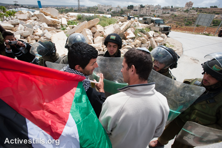 A Palestinian and a Jewish Israeli activist confront Israeli soldiers during a weekly demonstration against the Israeli occupation and Separation Wall in the West Bank village of Al Ma'sara, April 5, 2013. The Wall, if built as planned, would cut off the village from its agricultural lands. (photo: Ryan Rodrick Beiler/Activestills.org)