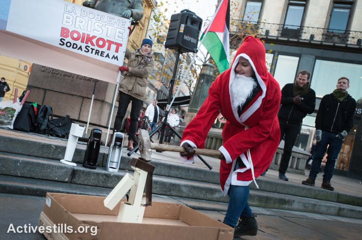 A Norwegian activist in a Santa suit uses a sledge hammer to smash SodaStream appliances in front of the Norwegian Parliament building in Oslo, December 6, 2014. Boycott, Divestment and Sanctions (BDS) activists have targeted SodaStream, which makes home soft drink carbonation appliances, because one of their factories is located in the West Bank industrial settlement Mishor Adumim. All Israeli settlements in the occupied Palestinian territories are illegal under international law. (photo: Ryan Rodrick Beiler/Activestills.org)